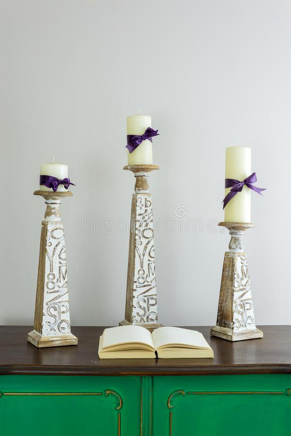 Three wooden candlesticks with engraved inscriptions holding three candles and opened book on green vintage wooden sideboard. Three wooden candlesticks with stock image