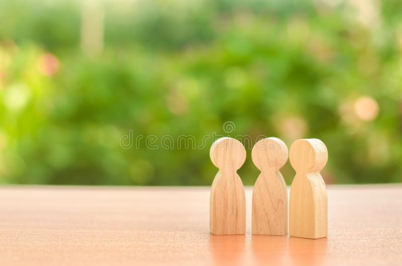 Three wooden figures of people stand on the background of nature. Communication, meeting place. conduct a conversation. Discussion. Of cases and plans, society stock photography