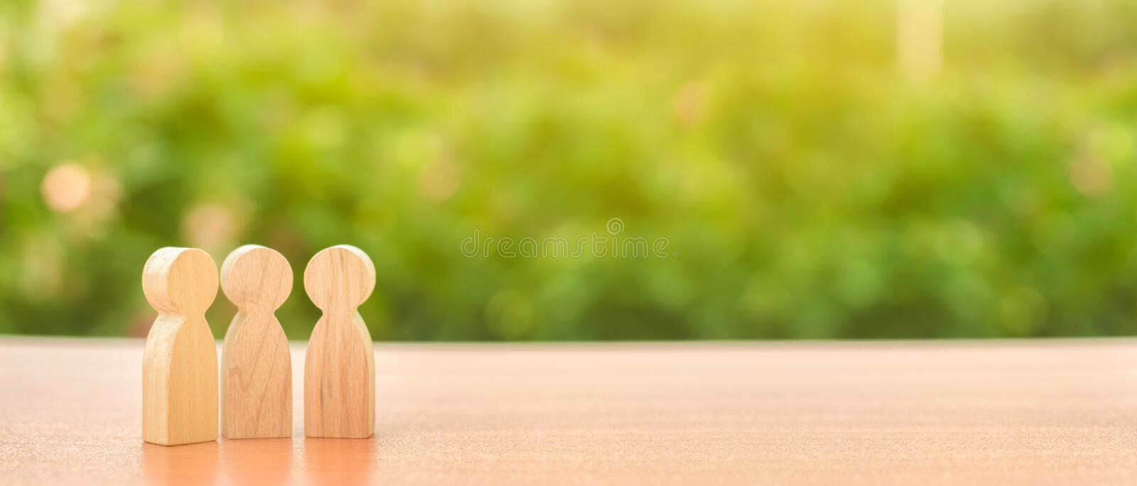 Three wooden figures of people stand on the background of nature. Communication, meeting place. conduct a conversation. Discussion. Of cases and plans, society royalty free stock photography