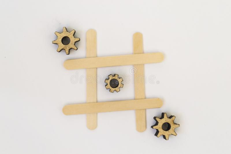 Three wooden gears from the mechanism lie in a row in a line in the game of tic tac toe, in a grid on a white background royalty free stock images
