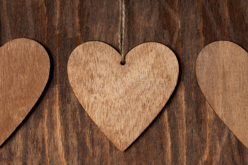 Three Wooden Heart With Rope On Wooden Background. Wooden Brown Heart With Rope On Wooden Background Close Up stock photos