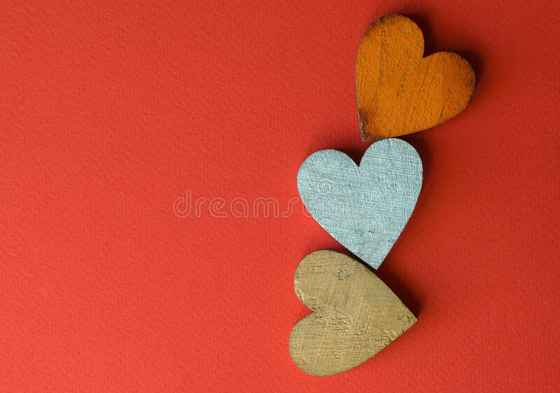Three wooden hearts on a red background. Greeting card for Valentine`s day. stock image