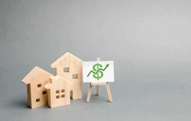 Three wooden houses figurines and a stand with green arrow up. Increasing the cost and liquidity of real estate. Attractive investing. rising prices or renting stock photos