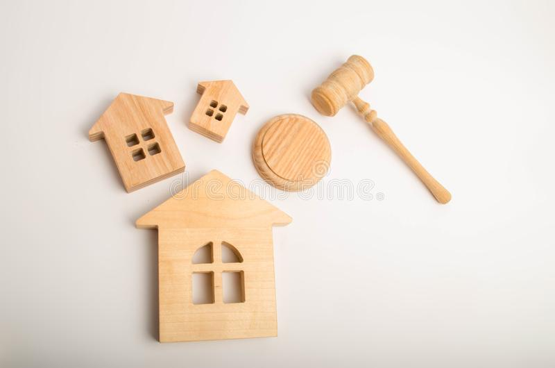 Three wooden houses and a hammer of the judge on a white background. Court cases on property and real estate. Confiscation and nat. Ionalization, real estate royalty free stock photography