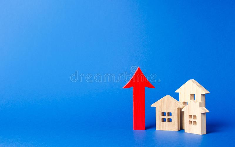 three wooden houses and red up arrow. High rates of construction, high liquidity. Supply and demand. prices for housing, building royalty free stock photos