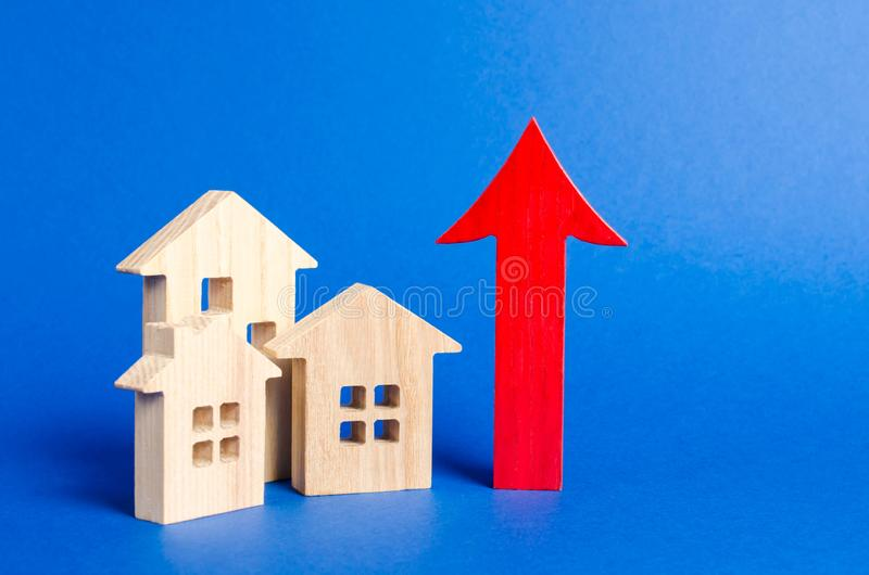 Three wooden houses and red up arrow. Real estate value increase. High rates of construction, high liquidity. Supply and demand. Prices for housing, building stock image
