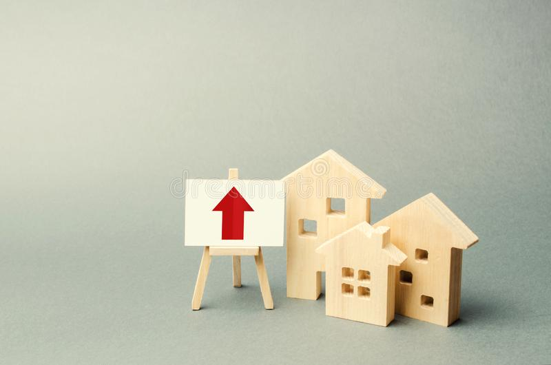 three wooden houses and a red up arrow on the sign. Real estate value increase. High rates of construction, high liquidity. Supply stock photos