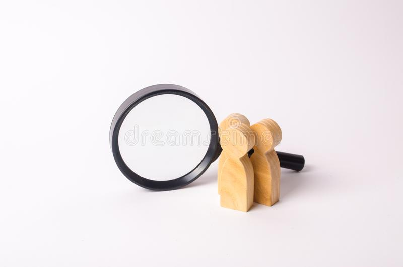 Three wooden human figure stands near a magnifying glass on a white background. The concept of the search for people and workers. stock image
