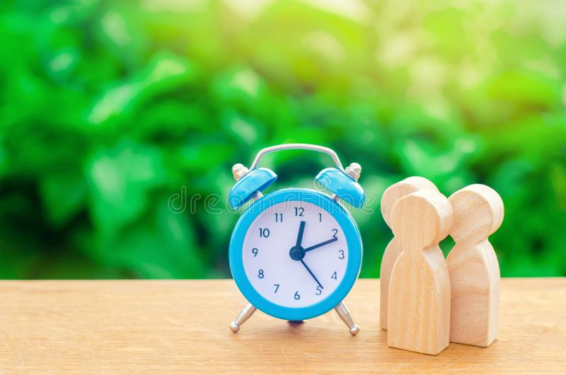 Three wooden human figures standing near a blue alarm clock on a green background. The concept of hopes and expectations. Queue. P stock photography