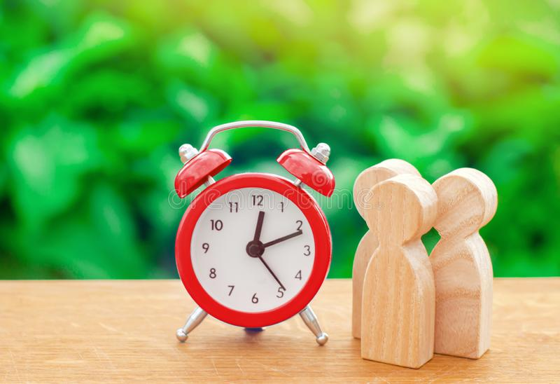 Three wooden human figures standing next to a red alarm clock on a nature background. Time concept. Business, Hourly payment royalty free stock photography