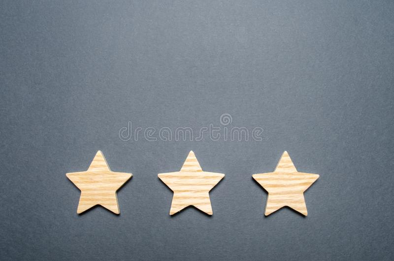 Three wooden stars on a gray background. The concept of quality and prestige. High quality and reliability, universal acceptance stock photo