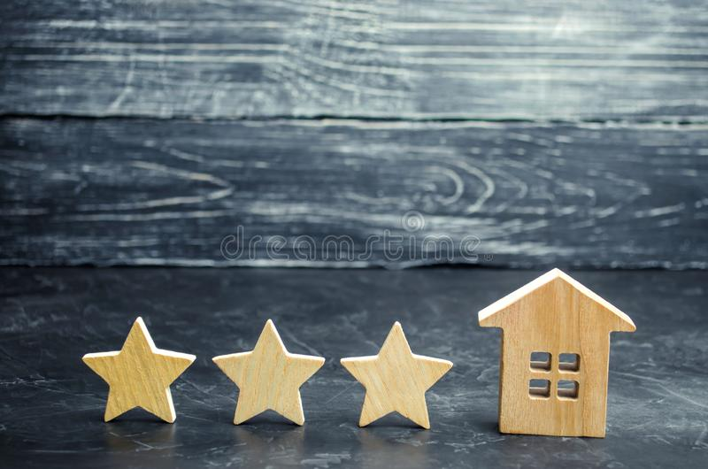 Three wooden stars and a house. Three star hotel or restaurant. Review of the critic. Quality of service and level of service. Rating of houses and private royalty free stock photos