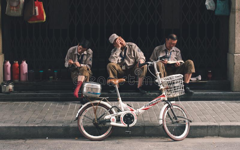 SHANGHAI, CHINA: Three workers break time, resting royalty free stock photography