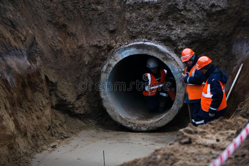Three workers install concrete gutters on the side of the road, power plants. Frame lifting concrete drainage pipe. Russia stock image