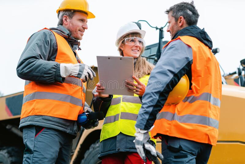 Three workers in a quarry discussing in front of heavy machinery royalty free stock photography