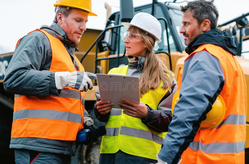 Three workers in a quarry discussing in front of heavy machinery stock photo