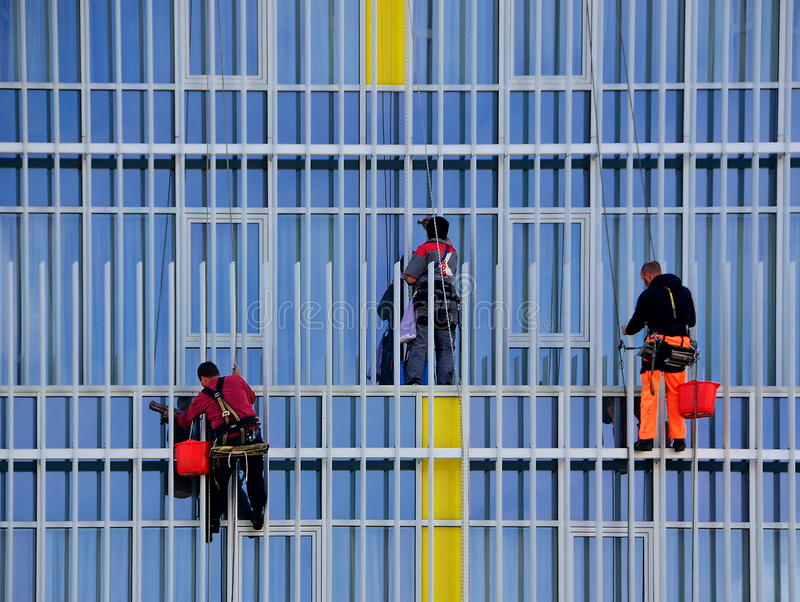 Three workers washing windows. On the buiding stock photos