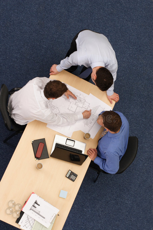 Three working business people over blue prints royalty free stock photo