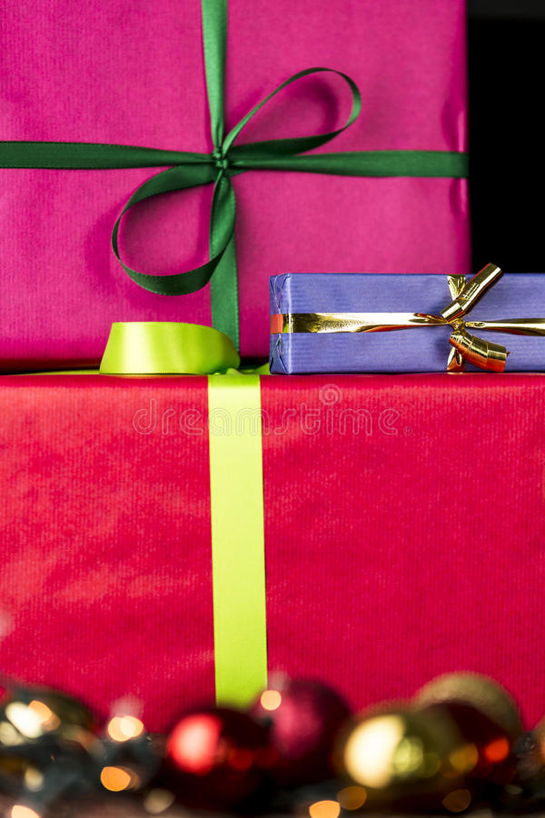 Three wrapped gifts, bowknots, spheres and glitters. The edgy, flat surfaces of three gifts wrapped in vibrant colors contrasting with the blurry specular royalty free stock photo