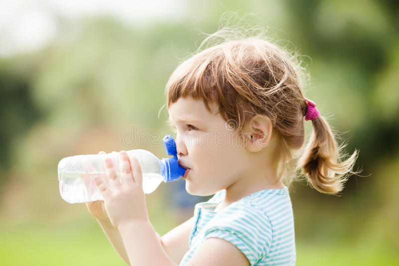 Three year child drinking from bottle royalty free stock photography