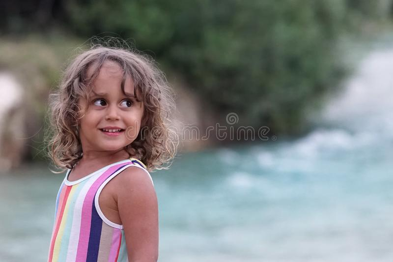 A three year old blond girl smiles looking from the side stock photography