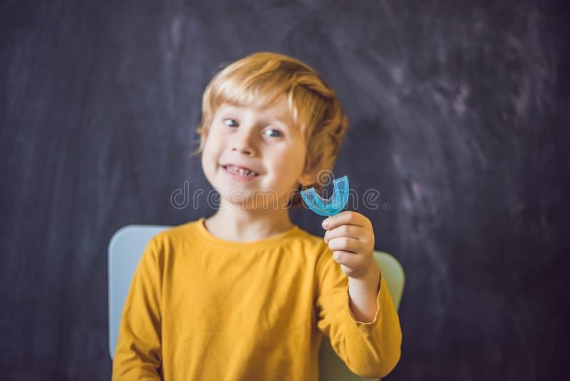 Three-year old boy shows myofunctional trainer. Helps equalize t. He growing teeth and correct bite, develop mouth breathing habit. Corrects the position of the stock photo