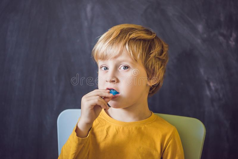 Three-year old boy shows myofunctional trainer. Helps equalize the growing teeth and correct bite, develop mouth. Breathing habit. Corrects the position of the stock images