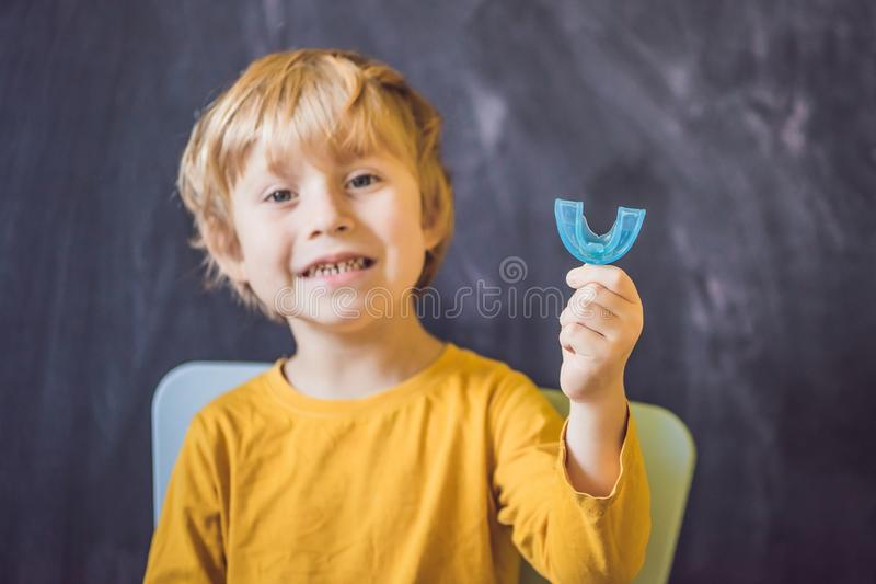 Three-year old boy shows myofunctional trainer. Helps equalize t. He growing teeth and correct bite, develop mouth breathing habit. Corrects the position of the royalty free stock photos