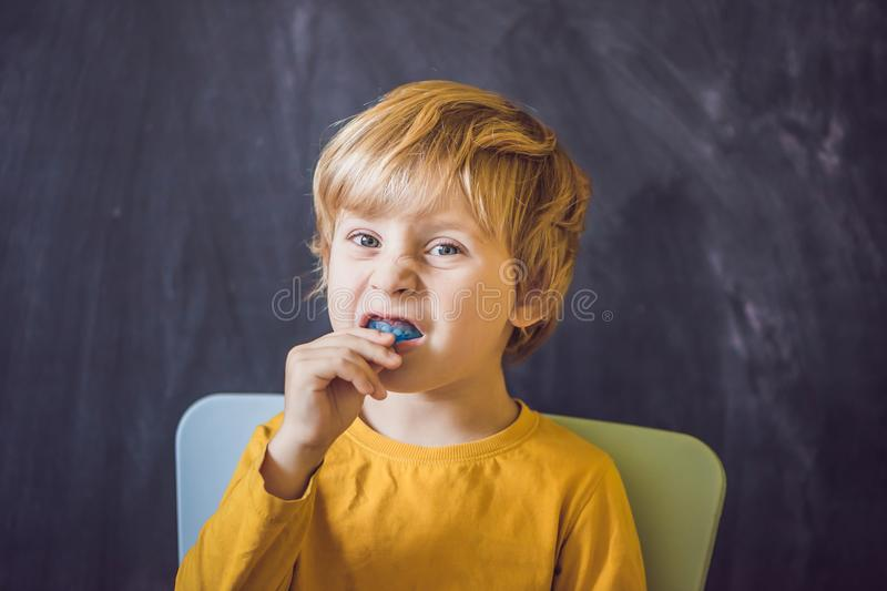 Three-year old boy shows myofunctional trainer. Helps equalize t. He growing teeth and correct bite, develop mouth breathing habit. Corrects the position of the stock images