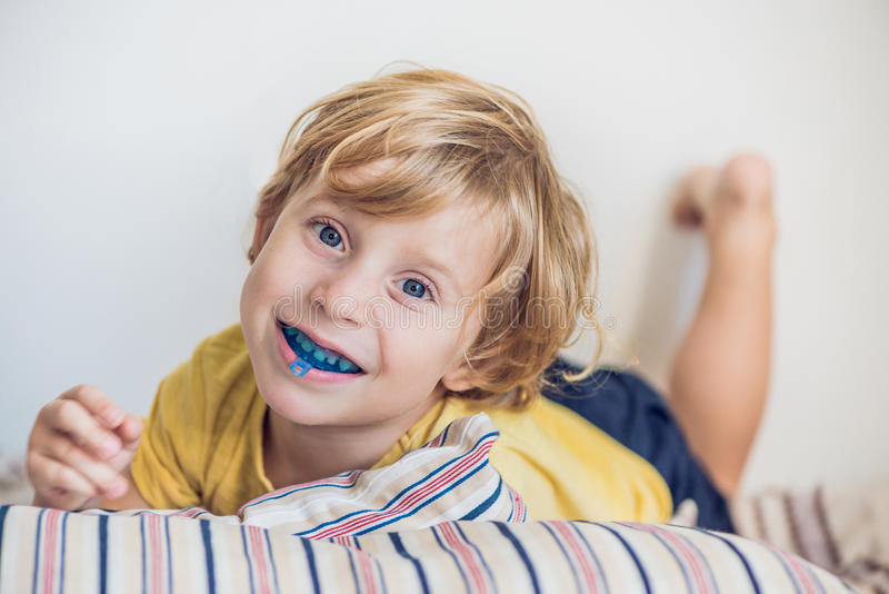 Three-year old boy shows myofunctional trainer to illuminate mouth breathing habit. Helps equalize the growing teeth and correct. Bite. Corrects the position of royalty free stock photo