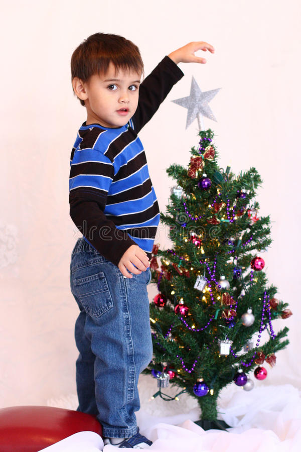 Three year old Christmas boy and little Christmas tree stock photos