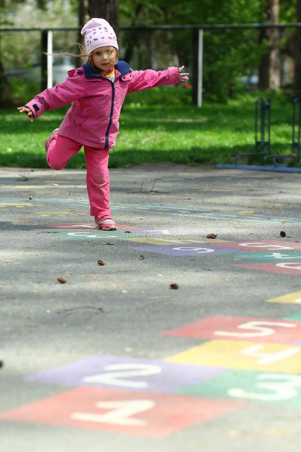 Three year old girl jumping and playing hopscotch in park royalty free stock image