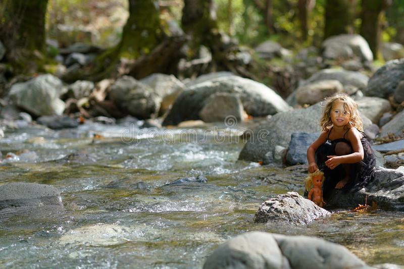 three year old girl playing with an old doll near a river in the beautiful nature of the Dirfi mountain in Eubeoa royalty free stock images