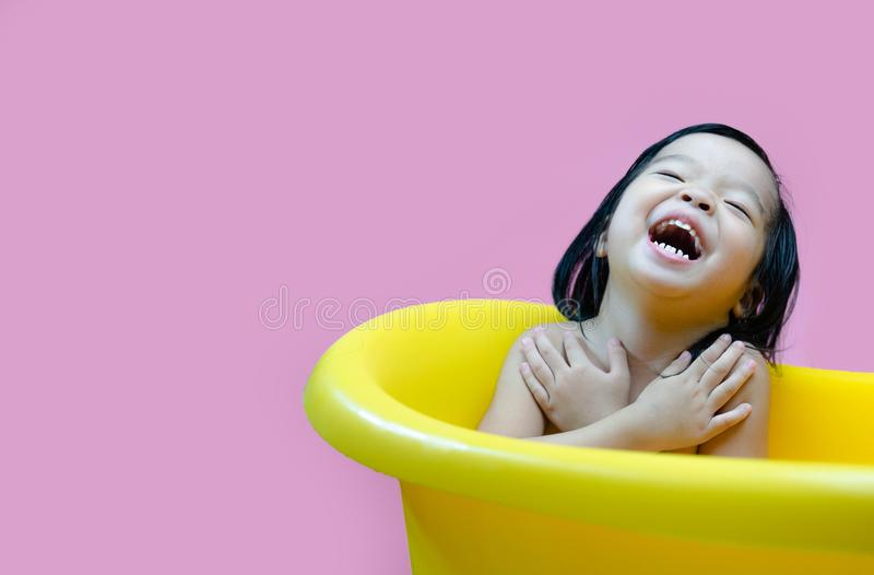 Three year old kid bathed happy in a yellow basin, Soap bubbles and kid bathing stock photo