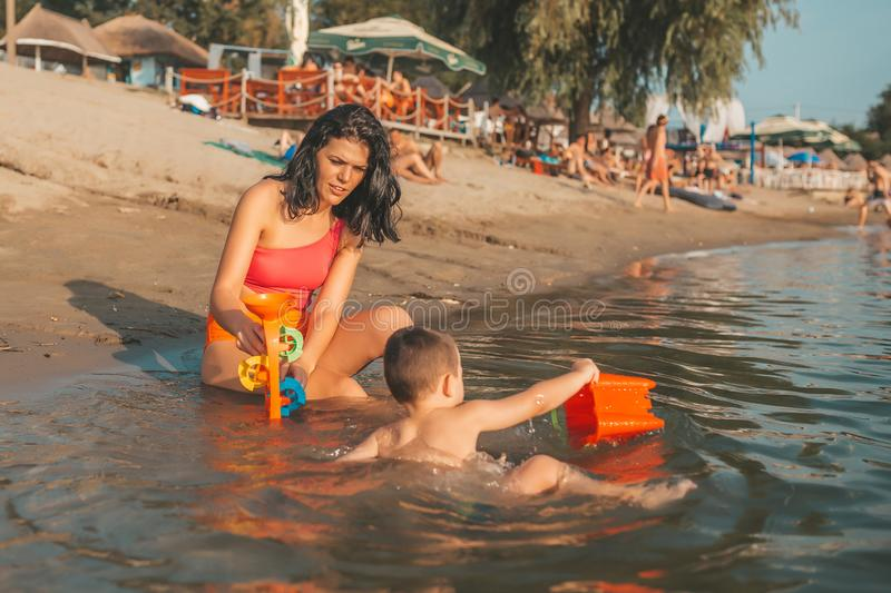 Three year old toddler boy playing with beach toys with mother in the water royalty free stock photos