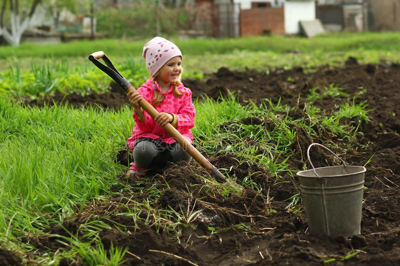 Three year old toddler girl in pink trying to dig the vegetable garden with a spade. Three year old toddler girl in pink trying to dig the vegetable garden with royalty free stock photos