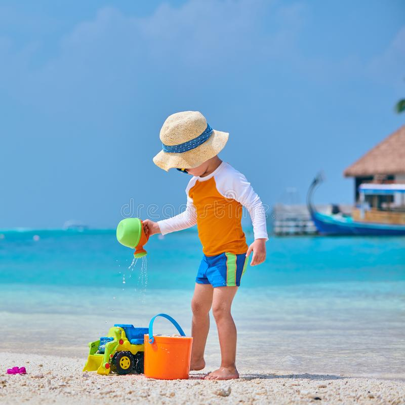 Three year old toddler playing on beach stock photo