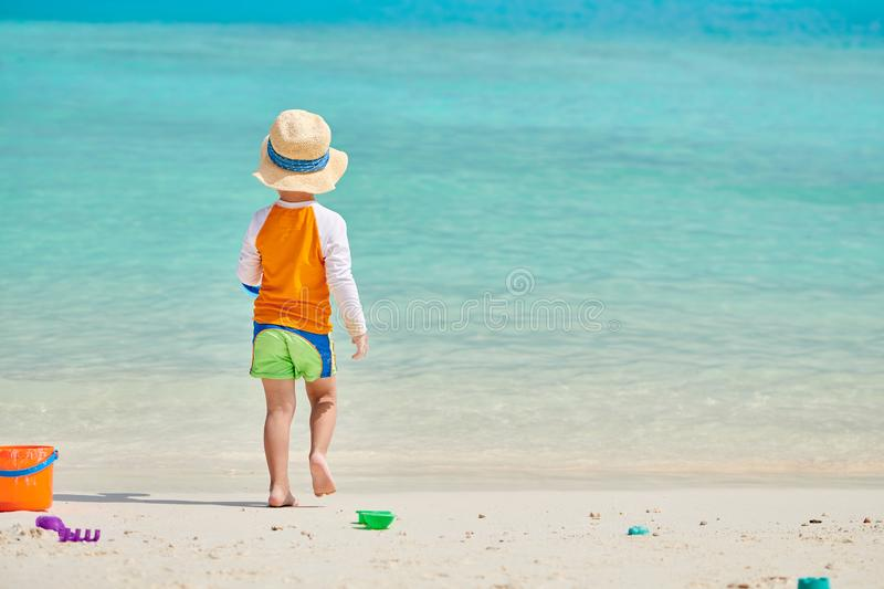 Three year old toddler playing on beach royalty free stock photo