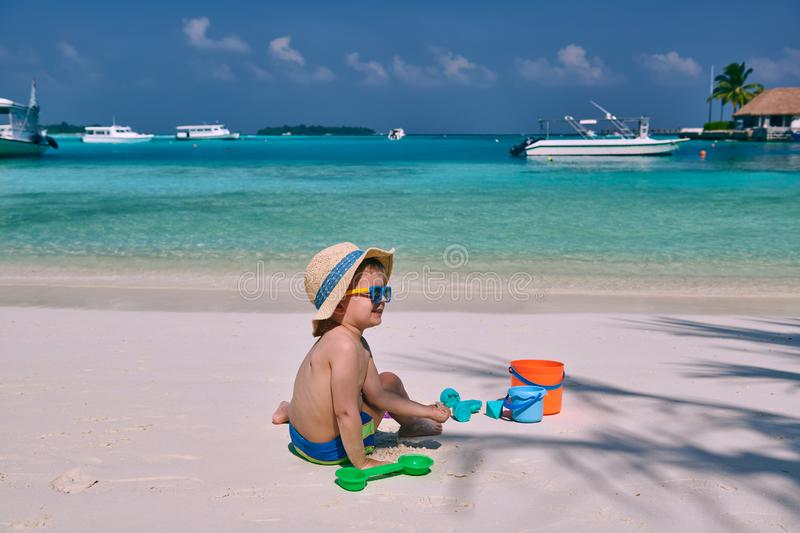 Three year old toddler playing on beach stock photos