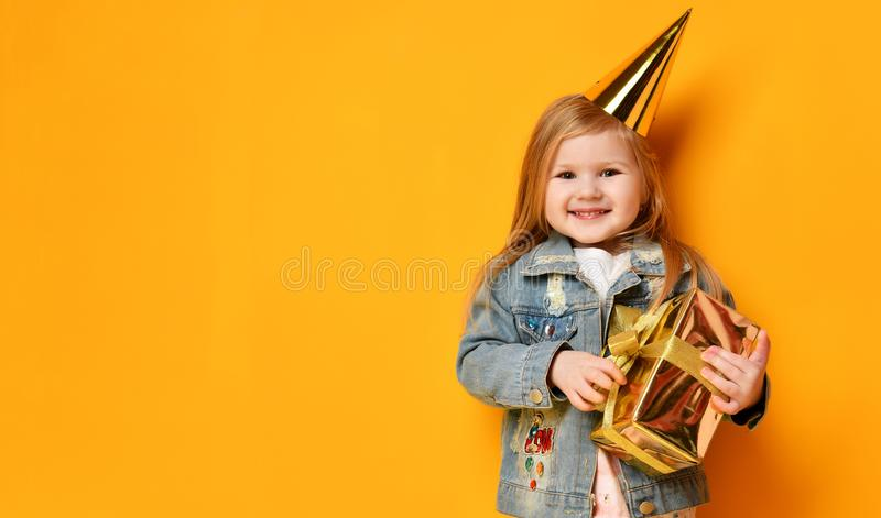 Three years girl toddler kid with gold present birthday cap celebrating. Three years girl toddler kid with gold present and birthday cap celebrating on yellow royalty free stock photo