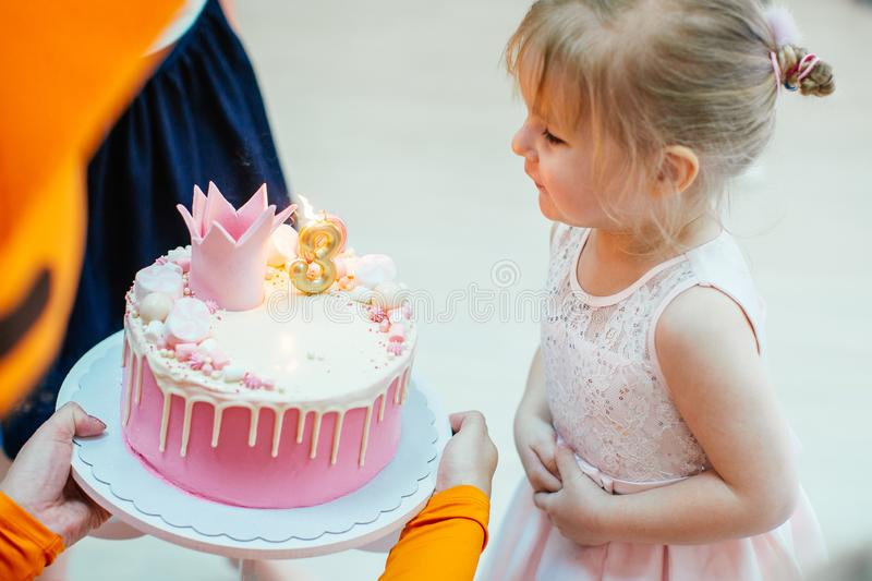Three years old blonde adorable girl in a pink dress blowing candles on birthday pink cake with number three stock photos
