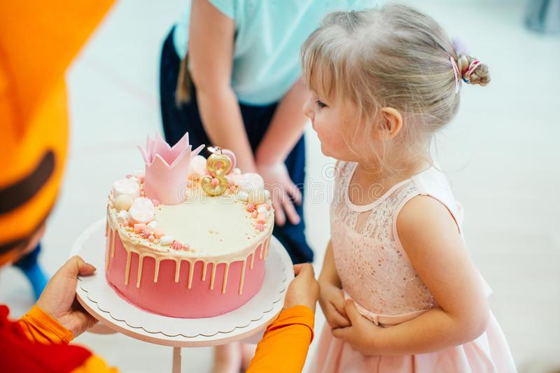 Three years old blonde adorable girl in a pink dress blowing candles on birthday pink cake with number three royalty free stock photo