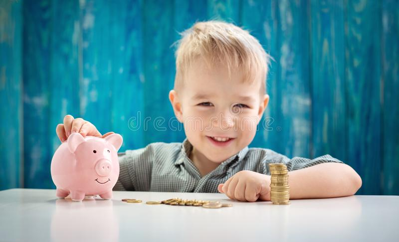 Three years old child sitting st the table with money and a piggybank royalty free stock photography