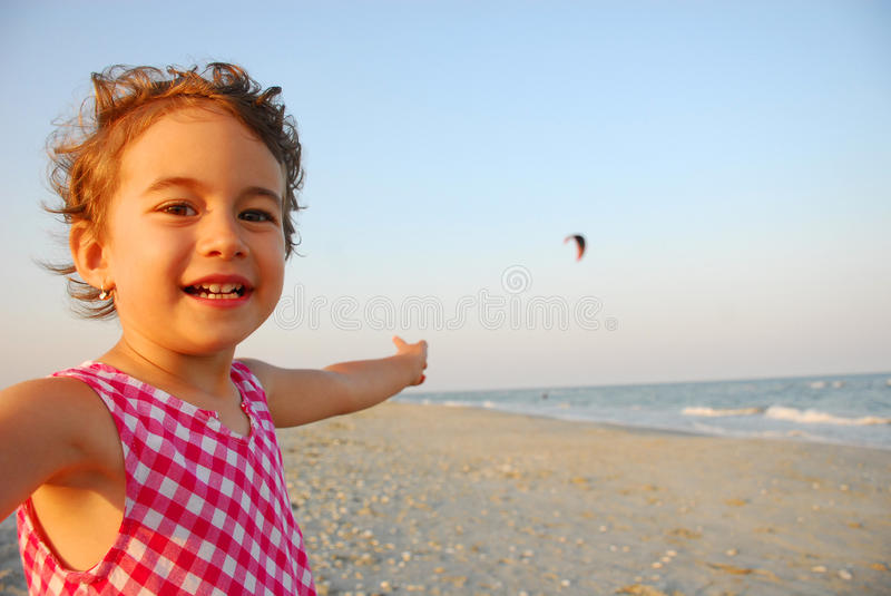 Three years old girl playing on the beach royalty free stock image