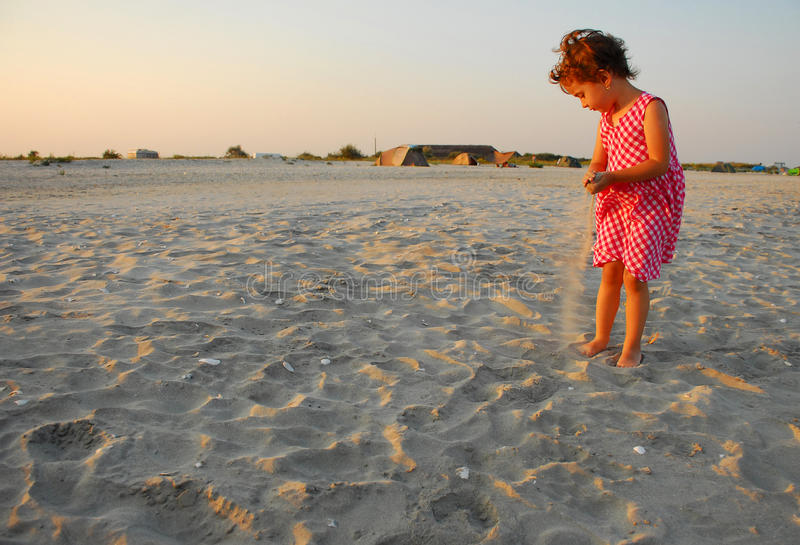 Three years old girl playing with sand stock photo