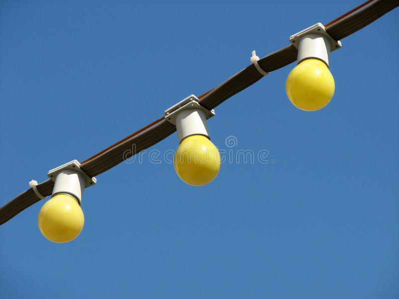Three yellow incandescent bulbs on the wire on blue sky background royalty free stock images