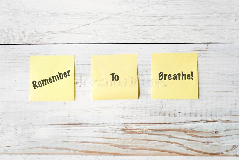 Three Yellow Post It notes with Message Remember to Breathe! royalty free stock photo