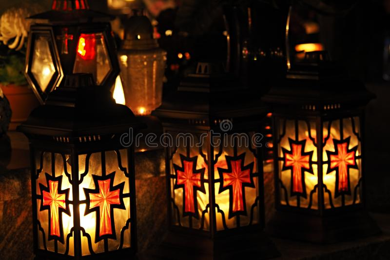 Three yellow and red grave candles in a cemetery at night royalty free stock image