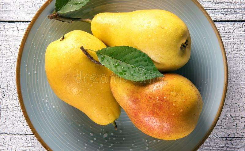 Close-up of three ripe pears on blue plate stock photos