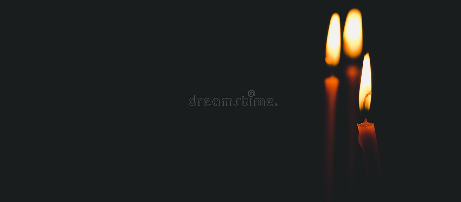 Three yellow wax candles burning with light of flame illuminate the space in the church, religion concept stock image
